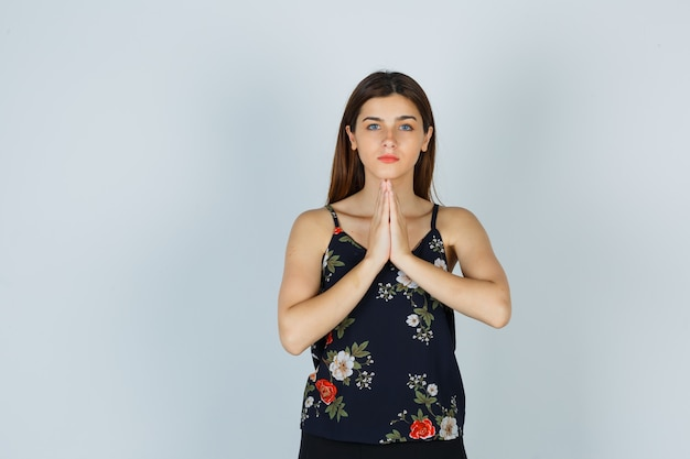 Attractive lady pressing hands together in praying gesture in blouse and looking thankful , front view.