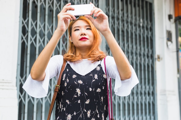 Attractive lady shooting on mobile phone