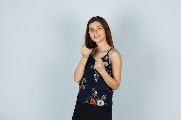 Signora attraente che mostra il gesto del vincitore in camicetta e sembra di successo. vista frontale.
