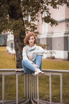 Attractive lady in street wear sitting on rail