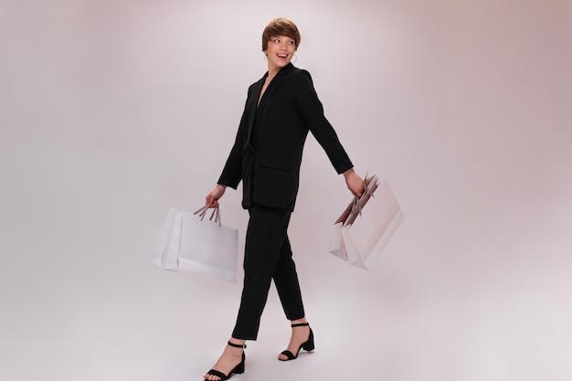 Attraente signora in tuta va a fare shopping con i sacchetti su sfondo isolato. ritratto a figura intera di donna dai capelli corti in giacca e pantaloni neri si muove su sfondo bianco