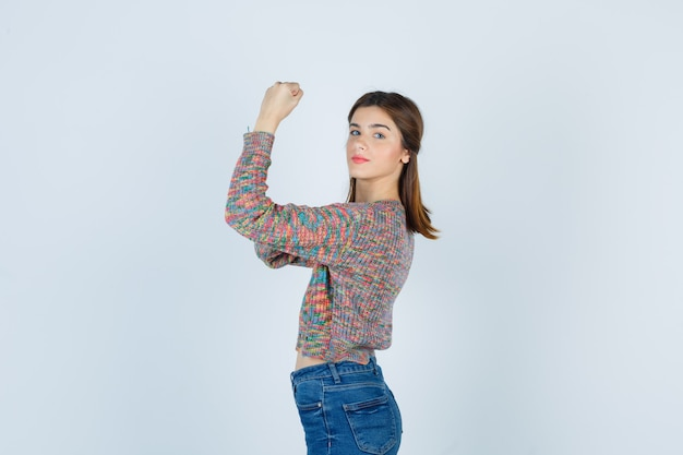 Attractive lady in sweater, jeans showing her muscles and looking confident .