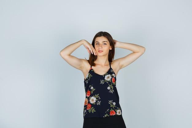 Signora attraente che tocca la guancia, tenendo la mano dietro la testa in camicetta e guardando affascinante, vista frontale.