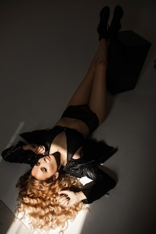 Attractive lady in underwear and leather jacket lying on a light spot on white surface. fashion concept