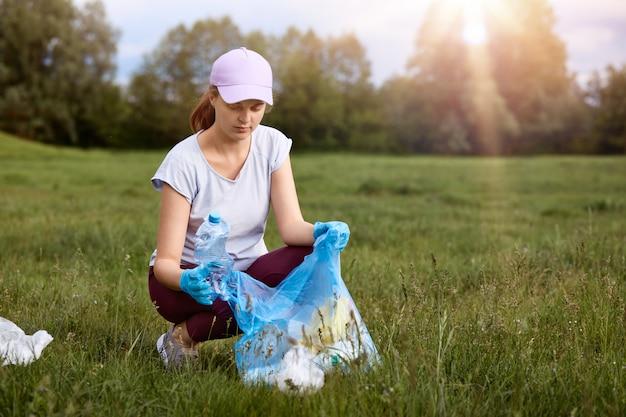 Привлекательная женщина в белой повседневной футболке, бейсболке и брюках, собирает использованный полиэтиленовый пакет, чистит грязный луг, женщина выглядит сосредоточенно, помогает планете.