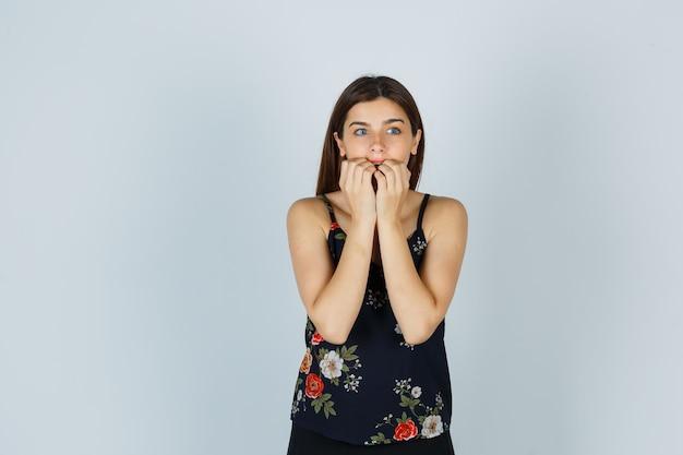 Signora attraente mentre guarda da parte mangiarsi le unghie in camicetta e sembra eccitata. vista frontale.