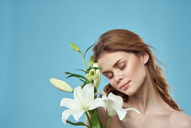 魅力的な女性の白い花青い背景の肖像画のトリミングされたビュー