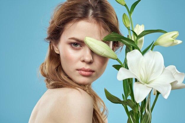 魅力的な女性の白い花青い肖像画のトリミングされたビュー