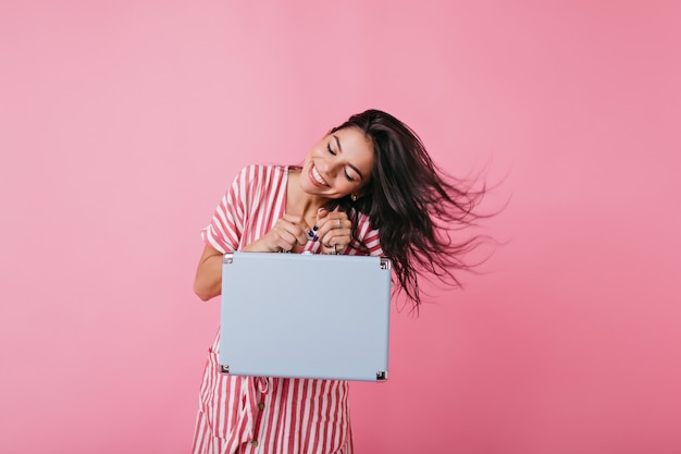 Attractive lady with bright snow-white smile plays hair. shot of european tanned model in summer outfit with hand luggage.
