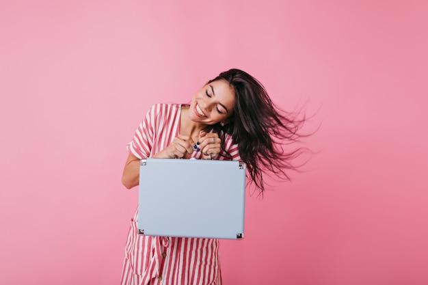 真っ白な笑顔の魅力的な女性が髪を弾きます。機内持ち込み手荷物付きの夏服のヨーロッパの日焼けモデルのショット。