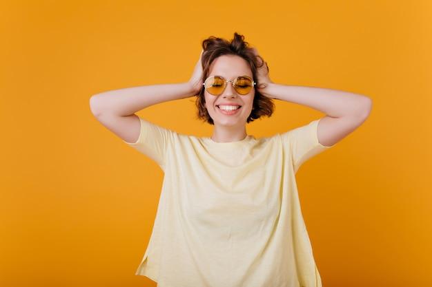 행복을 표현하는 검은 물결 모양의 머리를 가진 매력적인 아가씨. 오렌지 벽에 고립 된 노란색 복장에 행복 한 유럽 여자의 실내 초상화.