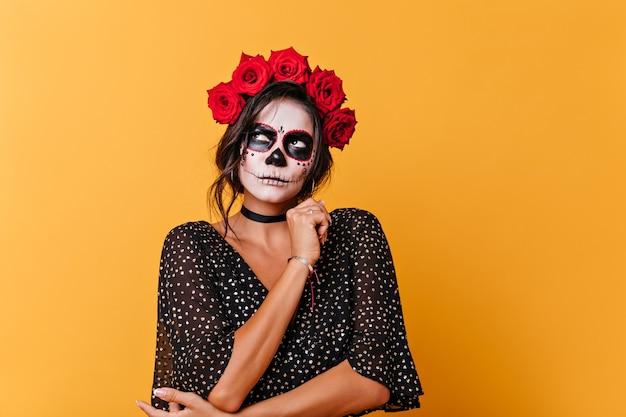 할로윈 메이크업으로 매력적인 아가씨는 신중하게 조회합니다. 오렌지 배경에 포즈를 취하는 그녀의 머리에 붉은 꽃을 가진 여자의 초상화.