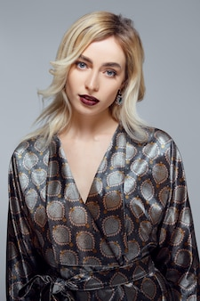 Attractive lady with long curly hair, clean fresh skin. blue eyes and dark red mat lips in silk bathrobe.