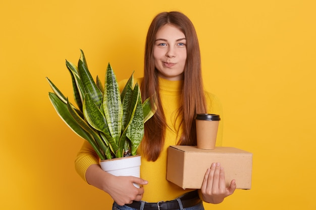 Attractive lady with long straight hair wearing yellow shirt,  with contemptuous facial expression, holding carton box, take away coffee and flower in hands.