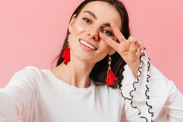 Привлекательная дама с красными большими серьгами улыбается и делает селфи на розовом фоне.