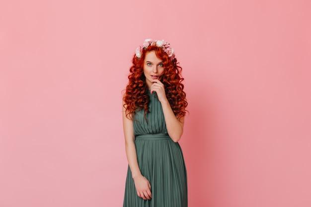 カメラを見て赤いカールと青い目を持つ魅力的な女性。ピンクの空間でポーズをとって長い緑のドレスと彼女の髪のバラの女性。