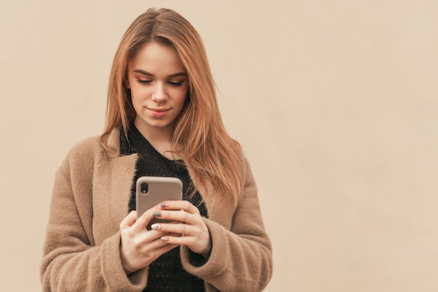 ベージュ色の背景に手でスマートフォンを持つ魅力的な女性。