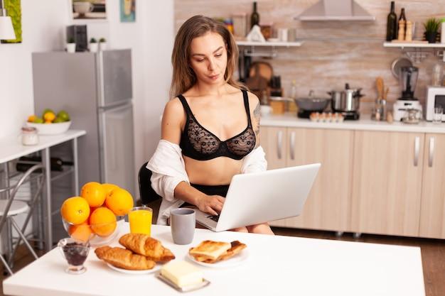 自宅のキッチンでラップトップを検索しているセクシーなランジェリーの入れ墨を持つ魅力的な女性。魅惑的な下着の笑顔に身を包んだキッチンに座ってpcに入れ墨を入力して魅力的なブロンドの女性