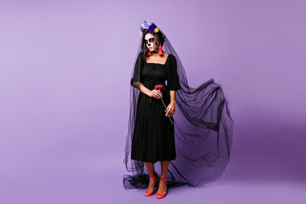 죽음의 날에 긴 검은 베일에 포즈 매력적인 라틴 소녀. 혼자 할로윈을 축하하는 매력적인 뱀파이어 아가씨.