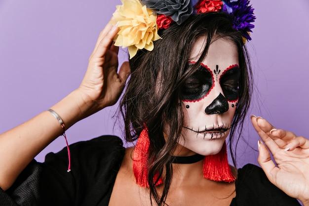 그녀의 얼굴에 특이한 예술을 가진 매력적인 라틴 아가씨가 보인다. 긴 붉은 귀걸이와 갈색 머리의 근접 촬영 초상화.