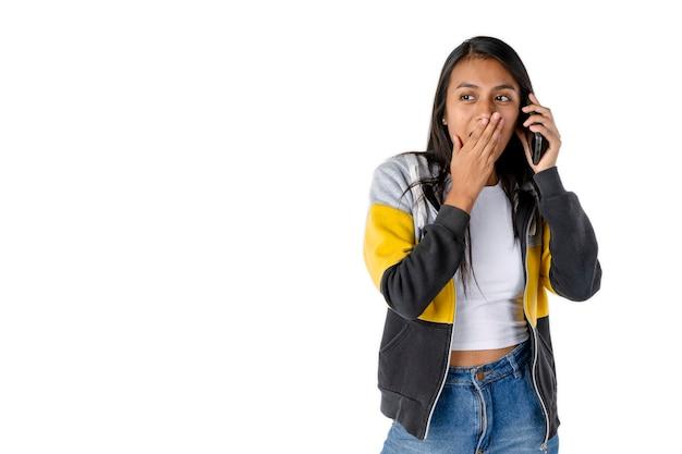 메시지를 듣는 동안 놀란 표정과 손으로 입을 가리는 매력적인 라틴 여성