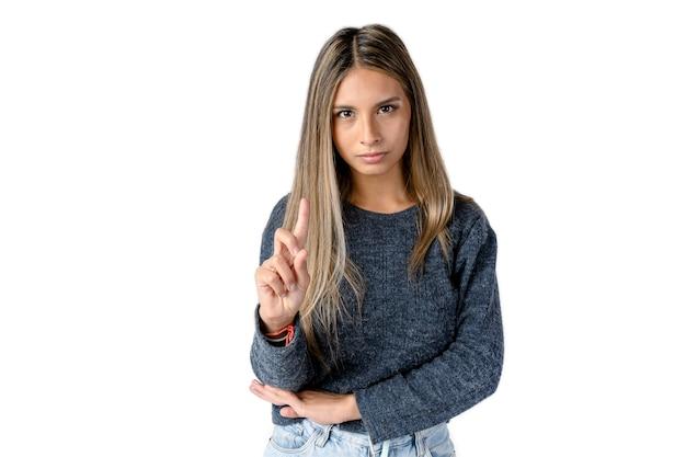 순수한 흰색 배경에 검지 손가락으로 no 사인을 하는 화나거나 진지한 표정을 가진 매력적인 라티나 여성. 스튜디오 사진.
