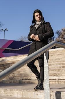 후드와 함께 계단을 내려오는 매력적인 라틴계 남자.