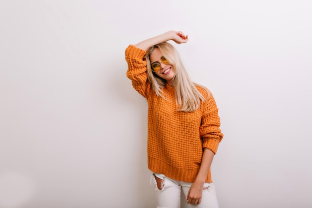 Attractive laughing woman in glasses leaning to white wall during photoshoot