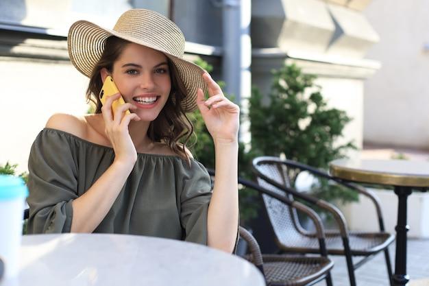 Привлекательная смеющаяся женщина разговаривает по мобильному телефону, сидя в кафе на открытом воздухе.