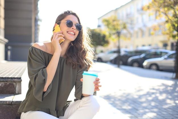Привлекательная смеющаяся женщина разговаривает по мобильному телефону, сидя на лестнице на открытом воздухе.