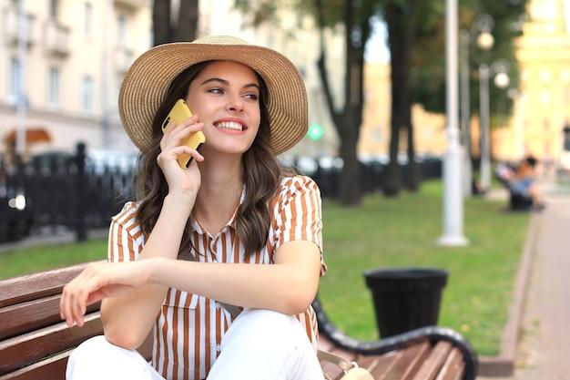 Привлекательная смех женщина разговаривает по мобильному телефону, сидя на скамейке на открытом воздухе.