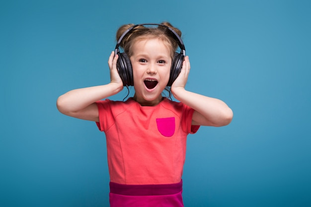 Attractive little cute girl in pink dress and headphones