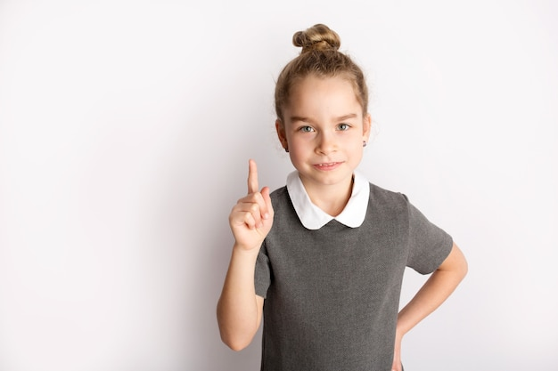 엄격한 학교 복장을 한 매력적인 어린 소녀는 흰색 배경에 서서 손으로 몸짓을 하고 얼굴에 행복한 표정을 존경합니다. 고품질 사진