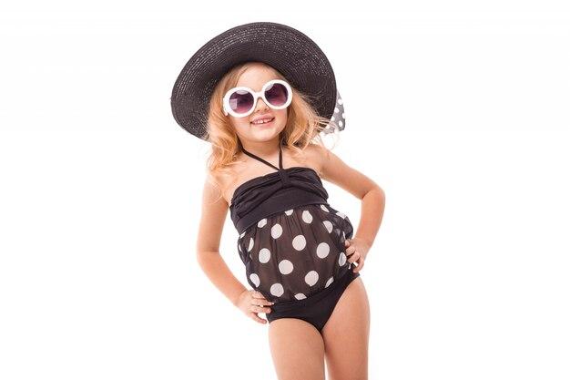 Привлекательная маленькая девочка в черном купальнике, белых очках и черной шляпе