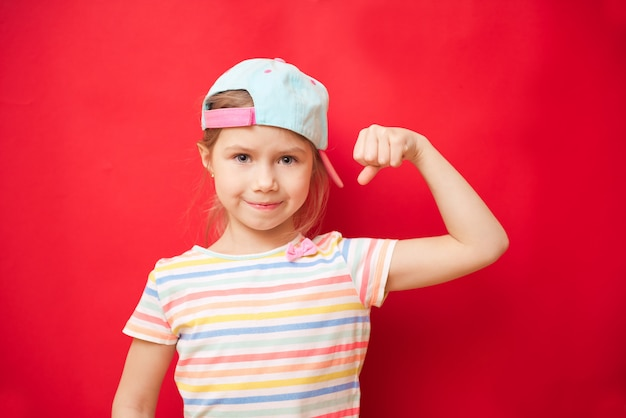 Attractive little girl shows the biceps. feel so powerful. girls rules concept. upbringing advices for girls. strong and powerful