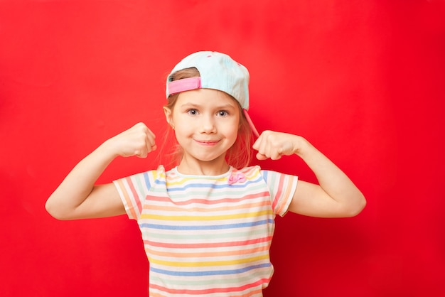 Attractive little girl shows the biceps on a red background. feel so powerful. girls rules concept. upbringing advices for girls. strong and powerful