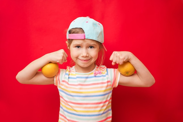 Attractive little girl shows the biceps on a red wall. feel so powerful. girls rules concept. upbringing advices for girls. strong and powerful