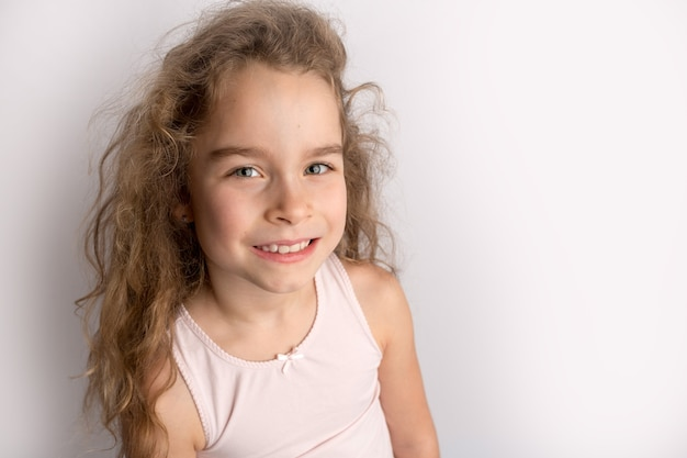 Attractive little girl stands on a white background, happy expression on her face with a beautiful smile, children crooked teeth, pediatric dentistry. high quality photo