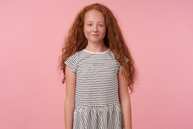 Attractive little redhead female kid with long curly hair posing over pink background with hands down, looking to camera with charming smile, wearing striped casual dress