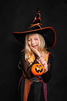 Attractive little witch with pumpkin