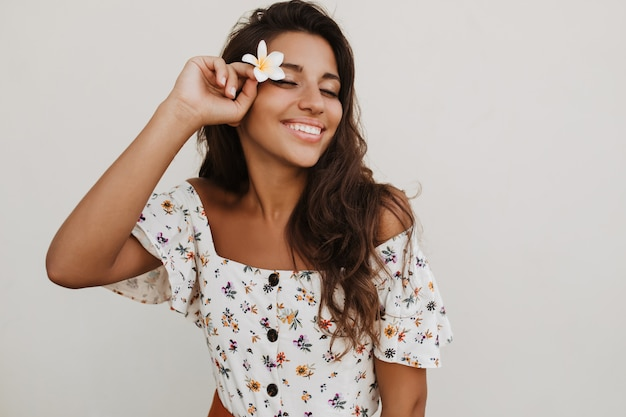 Attraente donna bruna dai capelli lunghi con segno di infinito sul polso sorridente sul muro bianco