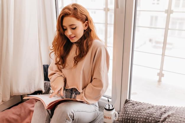매력적인 긴 머리 소녀 독서 잡지. 도 서와 함께 사랑스러운 생강 아가씨의 실내 초상화.