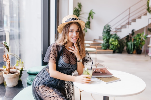 Attractive long-haired girl resting in restaurant and sitting at the table with magazines touching chin with fingers