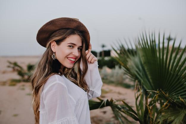 緑の植物の横に喜んでポーズトレンディな帽子で魅力的な長髪の笑う女性。砂漠を歩いて、笑顔の白いブラウスを着て愛らしい若い女性が休暇を楽しんでいます