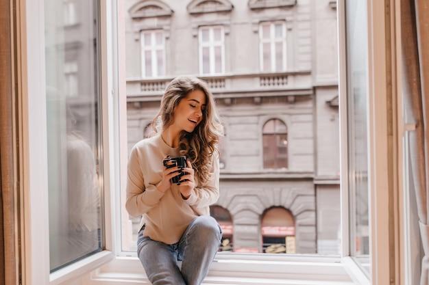 Attraente donna dai capelli lunghi che esprime emozioni felici, seduto sul davanzale