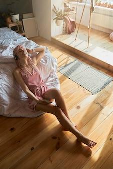 다리가 긴 매력적인 여성이 바닥에 침대에 기대어 좋아하는 음악을 듣습니다.