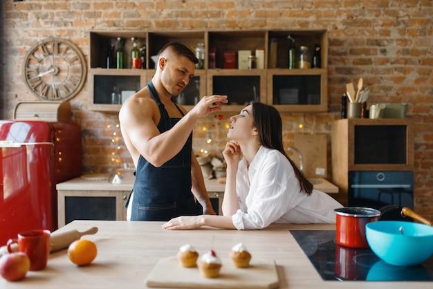 一緒にキッチンで料理の下着姿で魅力的な愛のカップル。裸の男性と女性が自宅で朝食を準備し、衣服なしの食品の準備