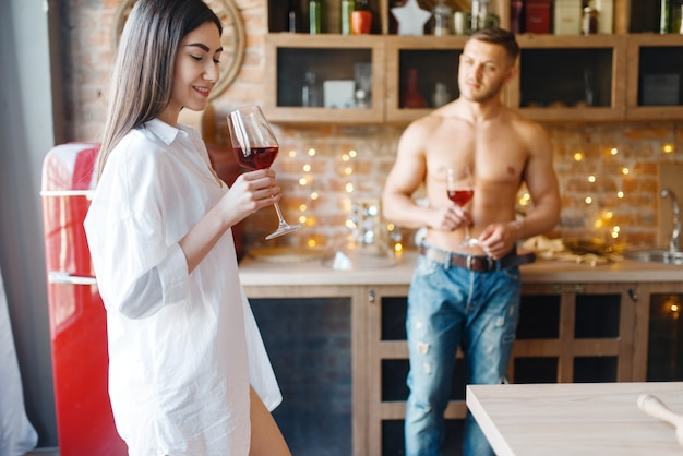 魅力的な愛のカップルは一緒にキッチンでロマンチックなディナーを過ごします。男と女の家で朝食を準備する、エロティシズムの要素を持つ食品の準備