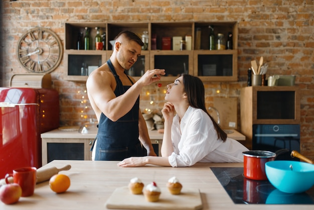 Attractive love couple in underwear cooking on the kitchen together. naked man and woman preparing breakfast at home, food preparation without clothes