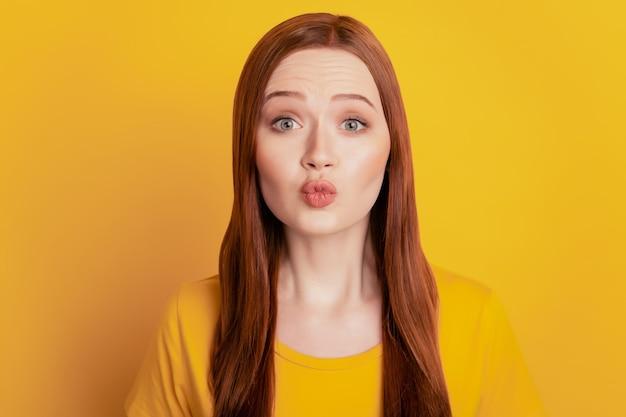 Привлекательная милая женщина отправить воздушный поцелуй на желтом фоне